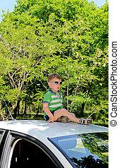 Boy on top of car