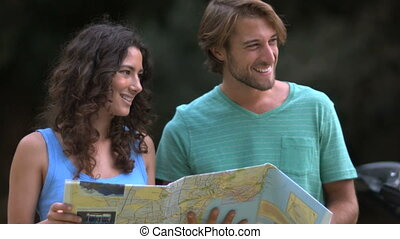 Couple reading a map and smiling