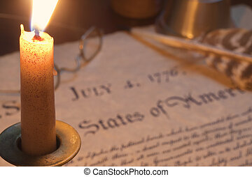 Selective focus view of the Declaration of Independence with a burning candle, glasses and a quill pen