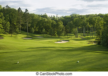 Golf green with bunkers in afternoon sunlight