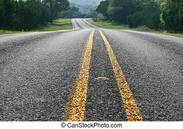 Low angle view of curving road in the Texas Hill Country -...
