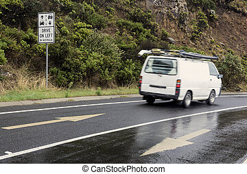 Drive on left in Australia sign and the white camper van