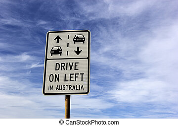 Drive on left in Australia sign seen against cloudy sky