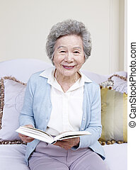 senior woman holding a book and smiling.