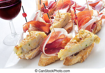 closeup of a plate with some typical spanish pincho de tortilla and pincho de jamon, spanish omelete and serrano ham served on bread