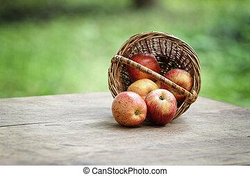 gala apples in a wicker basket, on wooden table