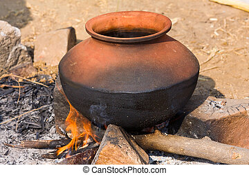 Clay pot with food on fire, India