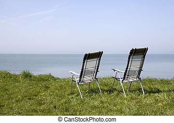 Two chairs looking out on the sea - Two empty chairs in...