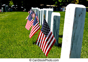 gravestone with US flags standing front