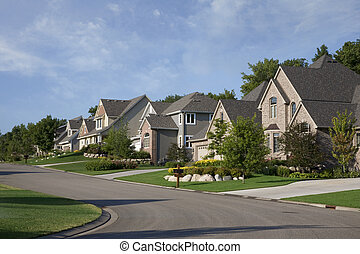 Houses on upscale suburban street in morning sunlight -...