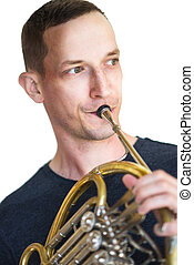 Caucasian male playing horn isolated on white