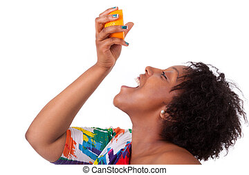 Overweight young black woman drinking orange juice , isolated on white background - African people