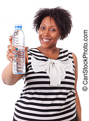 Overweight young black woman holding an water bottle, isolated on white background - African people