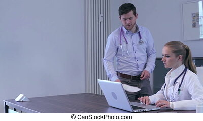 A male and a female doctor discussing in office