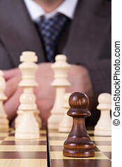 Businessman Focused on Pawn - Close up to chess pawn front...