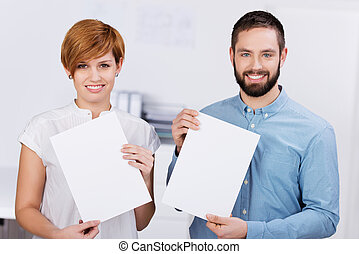 Businessman And Businesswoman Holding Blank Papers - Young...