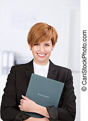 Businesswoman Holding Application Book In Office - Portrait...