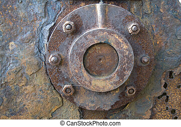 Rust - A peice of rusty metal with a round piece bolted to...