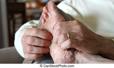 Massaging Foot - Man uses his fingertips to massage the...