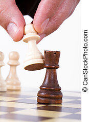 Hand Holding Pawn Against Castle - Close up view of...