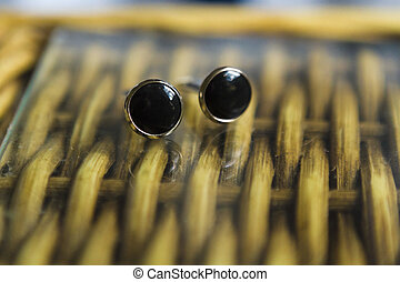 cufflink - Close up of a couple cufflinks on a wodden table