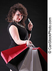 lovely woman with shopping bags over black background