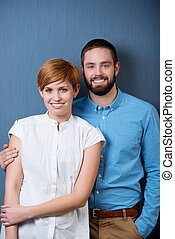 Smiling Couple Over A Blue Background - closeup portrait of...