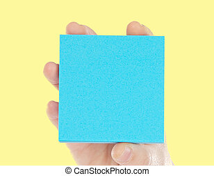 Hand holding a blue paper for notes