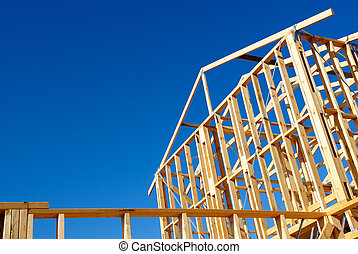 Wooden house frame against blue sky - New residential...