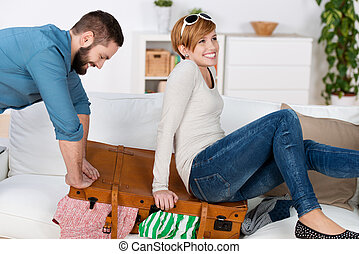 Couple Trying To Close Suitcase At Home - Happy young couple...
