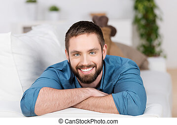 Young Man Lying On Sofa In House - Portrait of happy young...
