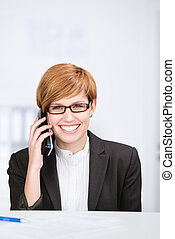 Businesswoman Using Cordless Phone At Office Desk