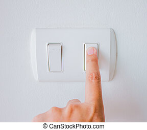 hand with finger on light switch, about to turn on the...