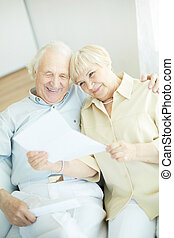 Reading letter - Portrait of a candid senior couple sitting...