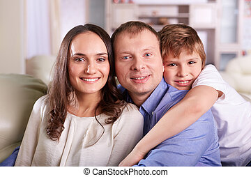 Affection - Portrait of happy family of three looking at...