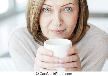 Mature woman - Portrait of mature woman with cup looking at...