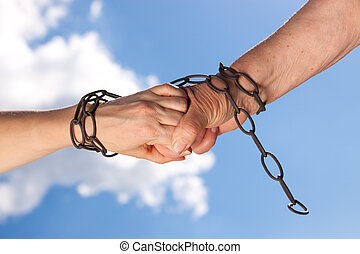 Two woman hands are chained together - Two female hands are...