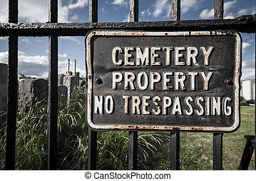 No trespassing sign on cemetary fence