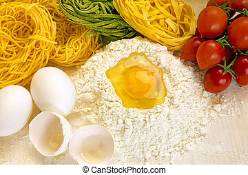 Ingredients for preparation of homemade egg pasta: flour,...