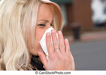 Blowing Her Nose - This young woman sneezing into a tissue...