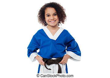 Little girl adjusting her brown karate belt - Smiling karate...