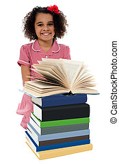 Portrait of pretty schoolgirl reading textbook