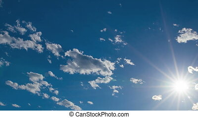 Blue cloudy sky with sunburst
