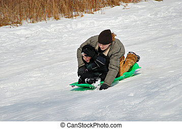 Sledding - Two children sledding down hill in winter snow