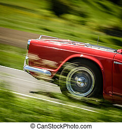 Car - Motion photo of red car driving along a country road.