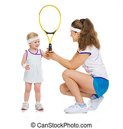 Mother giving baby tennis racket