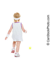Baby running for tennis ball rear view