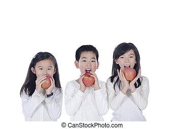 Three cute children eating an apples