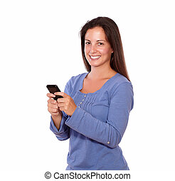 Lovely lady texting on cellphone while smiling - Portrait of...
