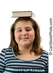 Good Student - A young girl balancing a text book on her...